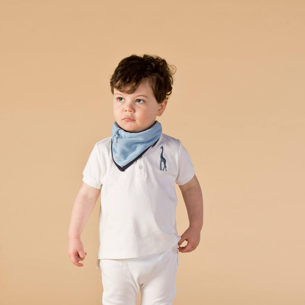 Boy wearing Oscar and Me pima cotton light blue bandana bib, white pants and polo