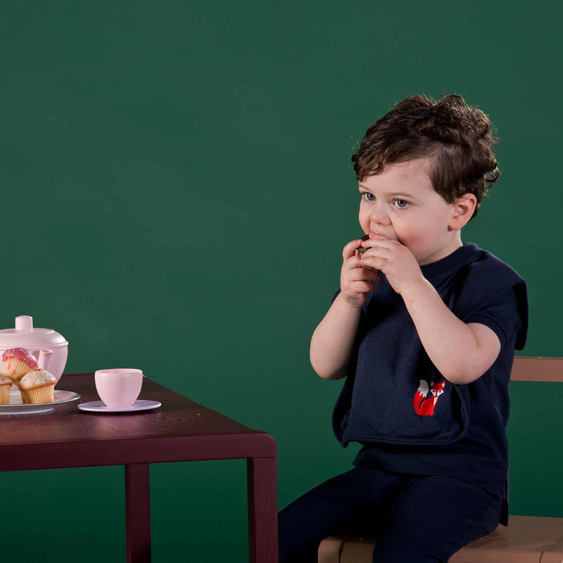 Boy wearing Oscar and Me navy eating bib, eating cupcake