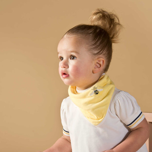 Girl wearing Oscar and Me pima cotton yellow bandana bib