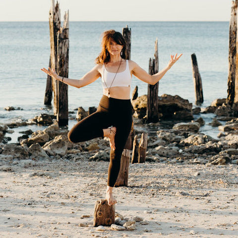 Mid standing in a yoga pose at the beach.