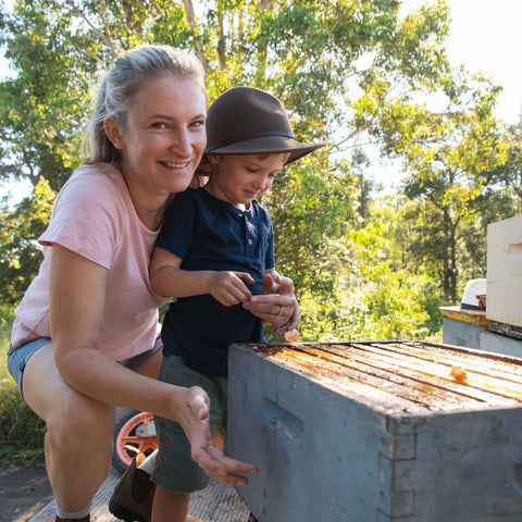 Gemma with her child, standing in front of bee hives.