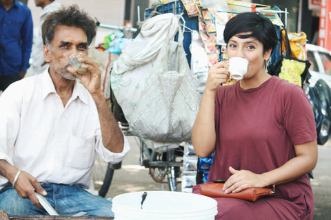 Man and woman sitting in a street in India drinking chai