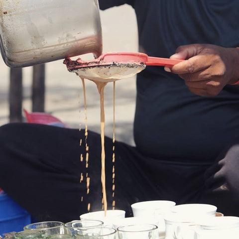 chai being strained through a strainer into lots of white teacups