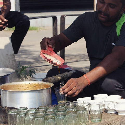 man pouring chai into glasses, at a tea stand in india