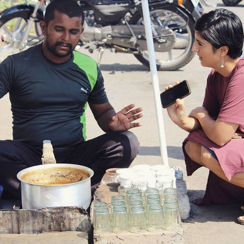 man and woman talking while sitting at a tea stand in India