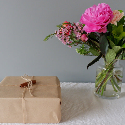 Wrapped Chai Walli gift in kraft paper, next to a bouquet of pink flowers.