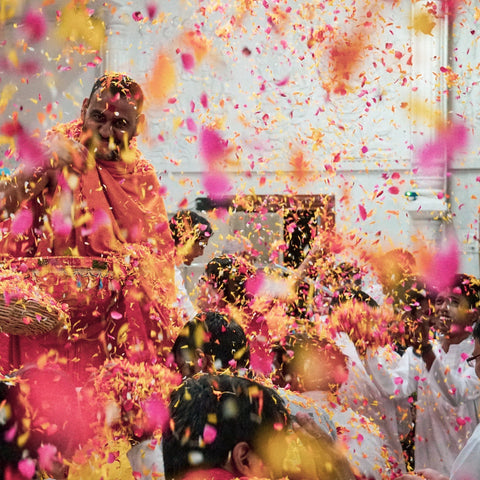 Pink and yellow powders being thrown into the air for Holi Festival.