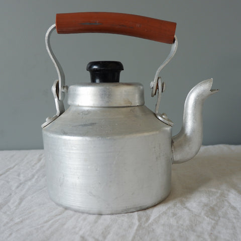 Traditional aluminium chai kettle with red handle.