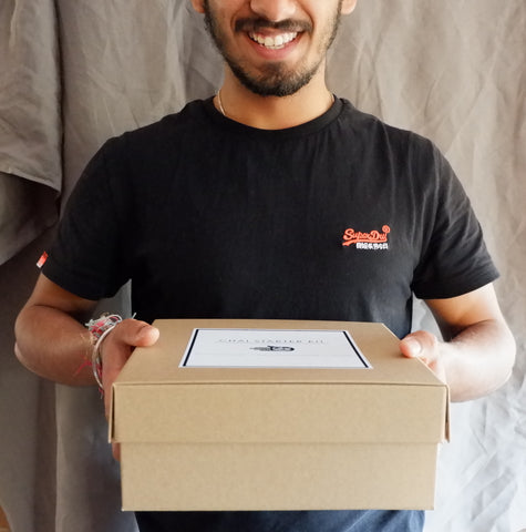 Man in black tshirt with a brown chai walli gift box