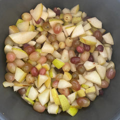 pears and grapes cut up in a pot ready to be made into jam