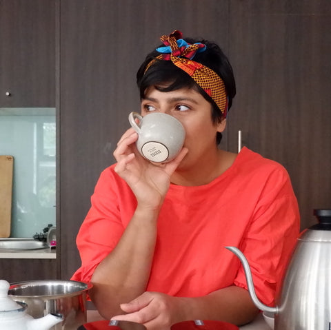 Uppma in a red top drinking a cup of chai