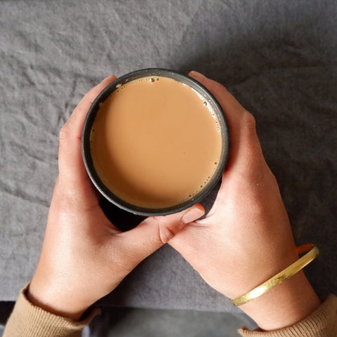 Two hands holding a cup of milky chai.
