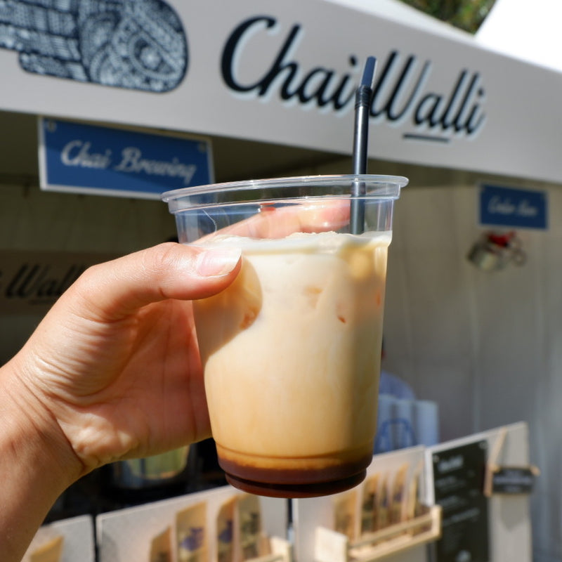 A hand holding an glass with ice tea made with chai syrup in it with the Chai Walli banner in the backdrop