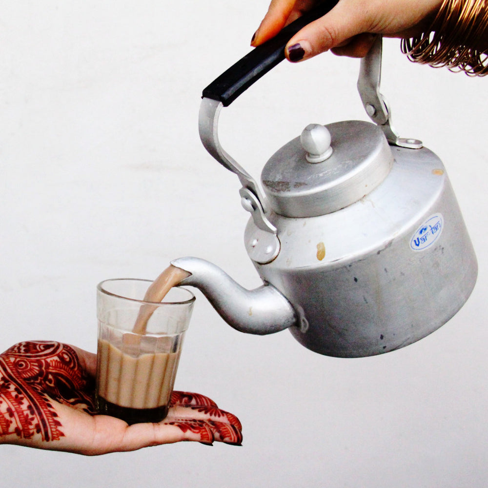 a henna decorated hand holding a chai glass while another hand pours chai in it from a kettle