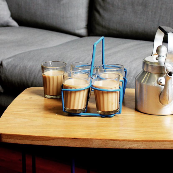 chai glasses with chai in a blue chai holder and a chai kettle on a table