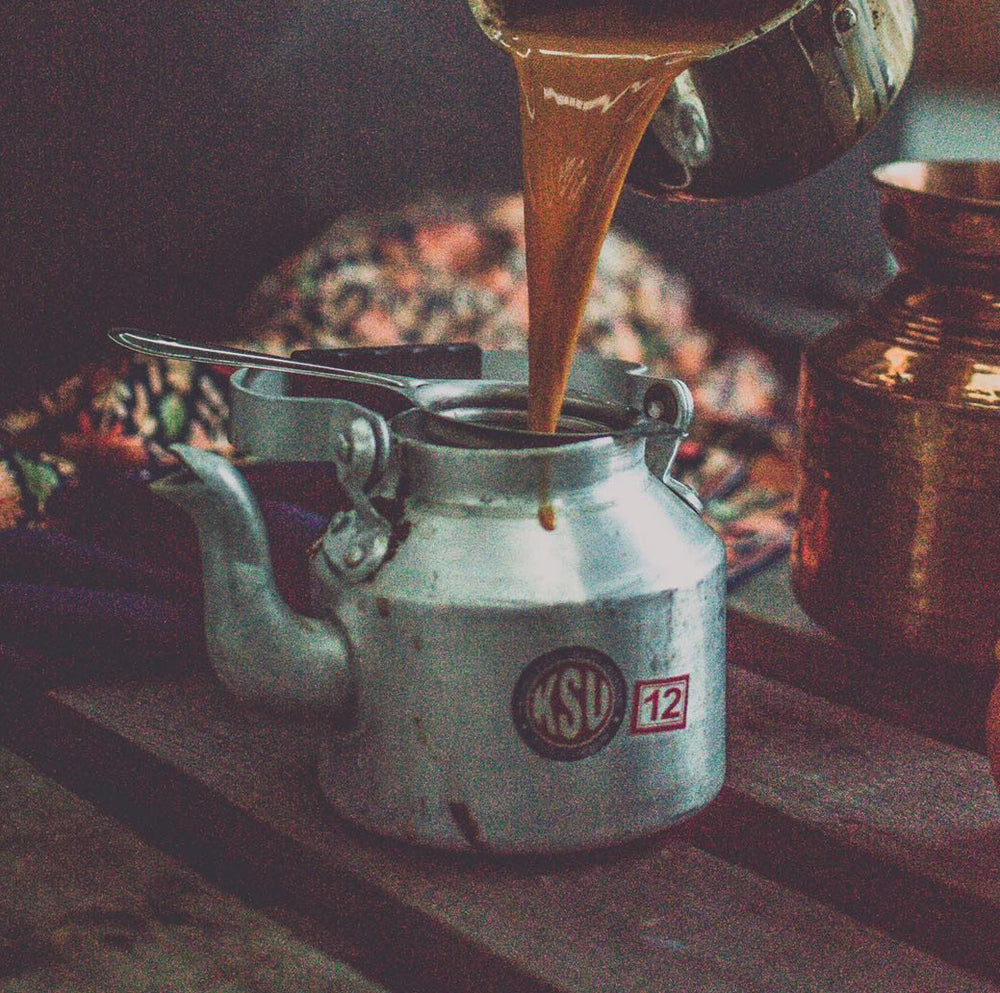 A chai kettle with chai being poured in it