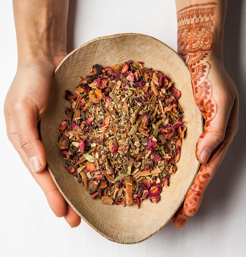 hands decorated in henna holding an oval dish containing the 11 spice chai caffeine free mix