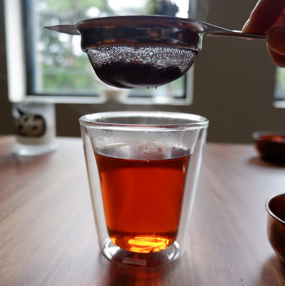 A glass with  Chai Walli English Breakfast black tea and a hand holding a strainer above it