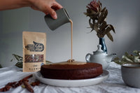 A hand pouring a caramel chai sauce on a chai sticky date pudding with the 11 spice chai product in the background