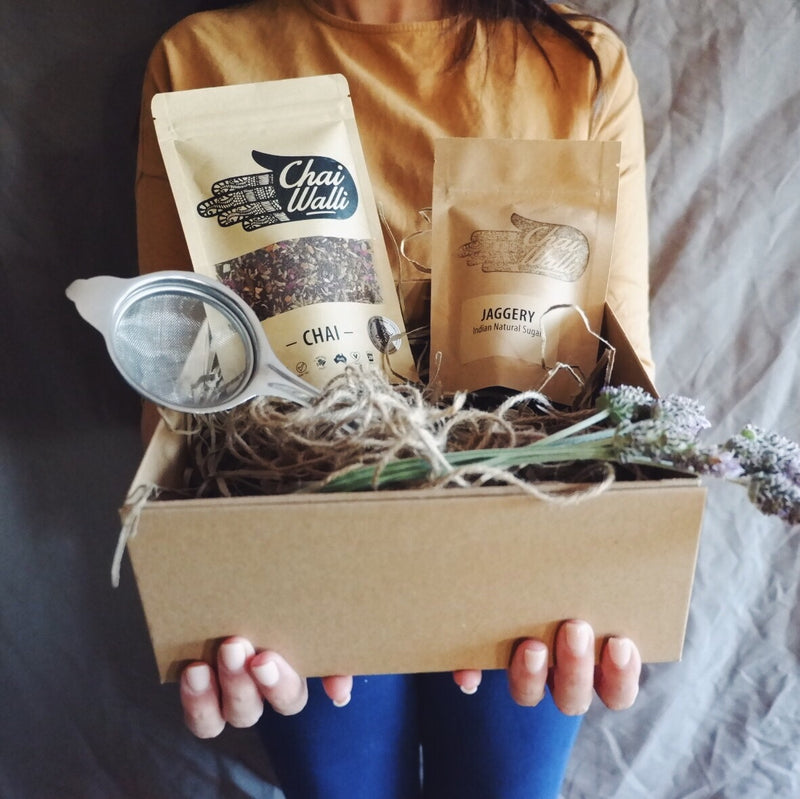 A girl holding the Chai Starter Kit with the products in it