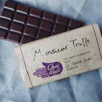 Chai Walli Chai Chocolate bar with its cover on the side on a grey tablecloth