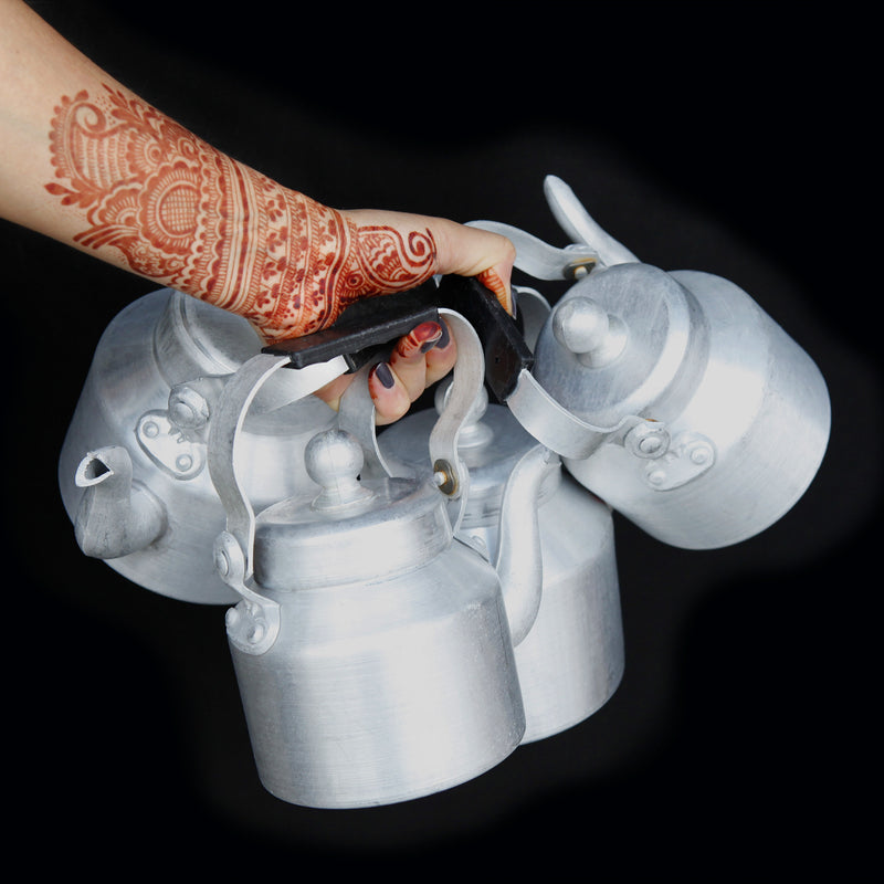 a henna decorated hand holding four chai kettles