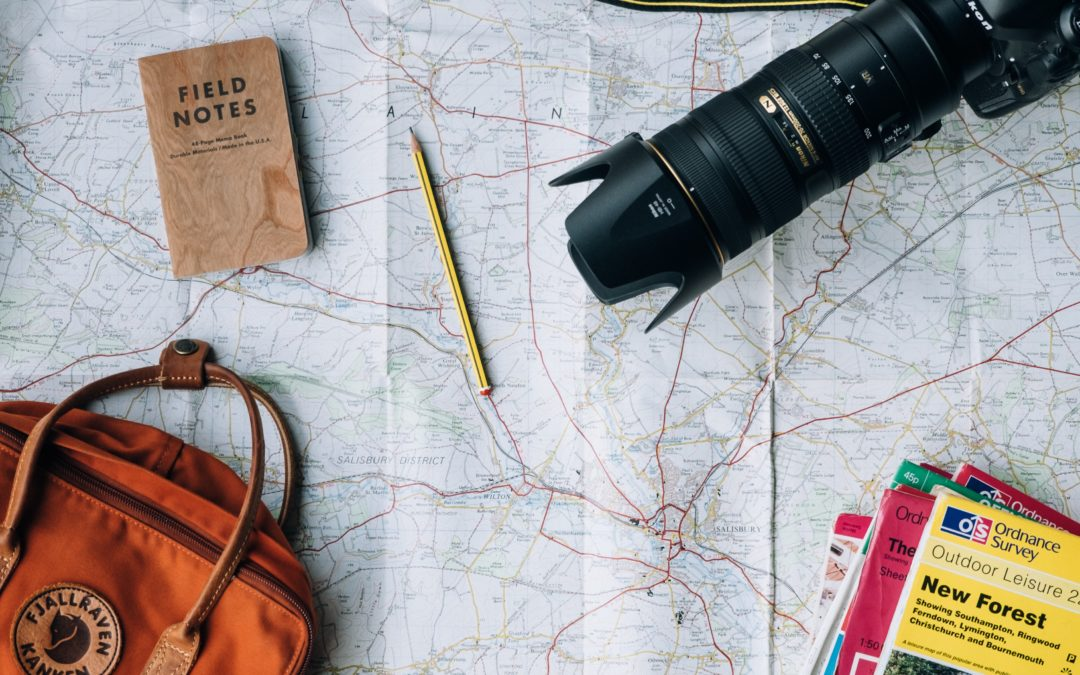 Destination map, travel bag, camera and books