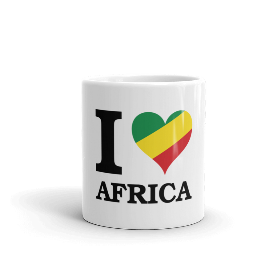 This coffee mug from Natty Wear is made of ceramic. The front print portrays the capital letter 'I' in black color, followed by a heart symbol (❤) in the Rastafarian colors (red, gold/yellow, green), which are also known as the Pan-African colors, below is the word 'AFRICA' set in capital letters in black color
