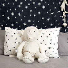 Child holding Severina Kids Off White Cotton Monkey sitting on bed setting with star pillow and garland in background