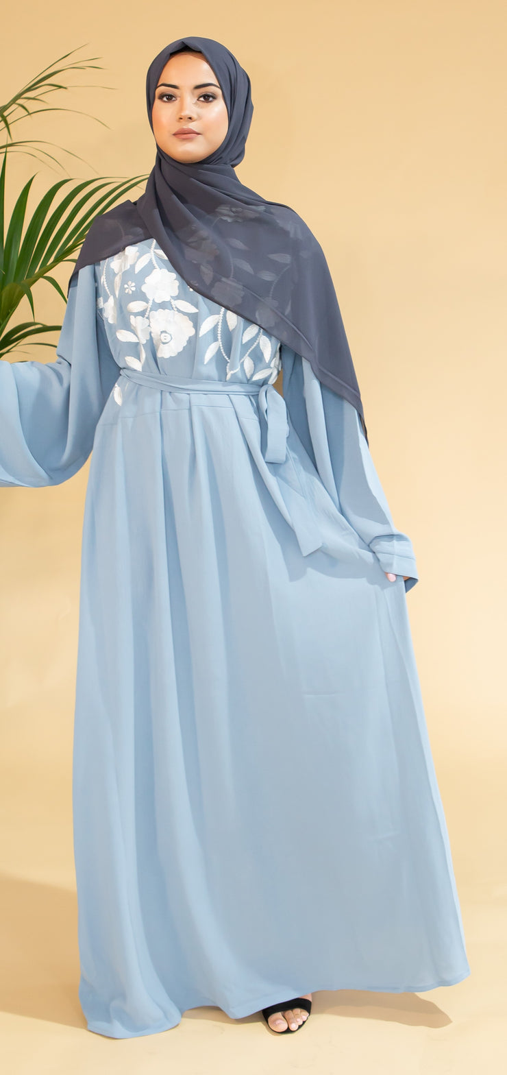 Aaliya Collections Blue Floral Abaya closed abaya of a pastel shade of blue with stunning contrasting white floral finishing
