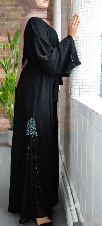 Aaliya Collections Silver Lining Abaya A stunning Classic Black abaya with side silver bead embellishment detailing finished with bead bordering creating a shimmery statement finish