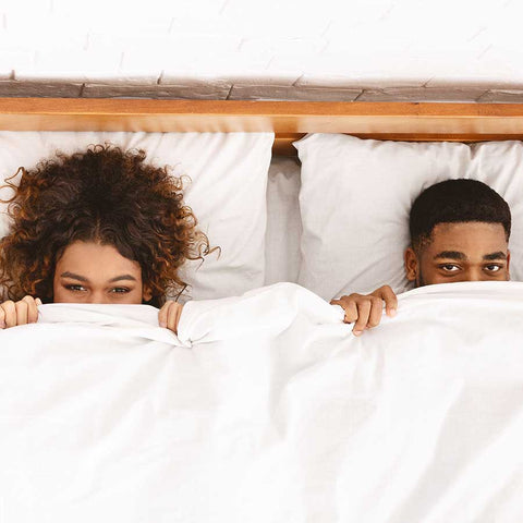 man and woman in bed covered in sheets