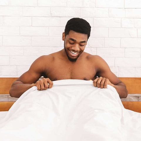 man looking at his penis in bed