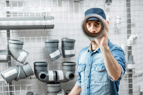 man looking into the pvc pipe
