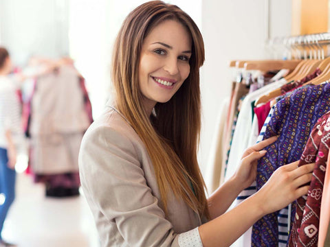 Woman smiling as she looks through clothes on a rack.