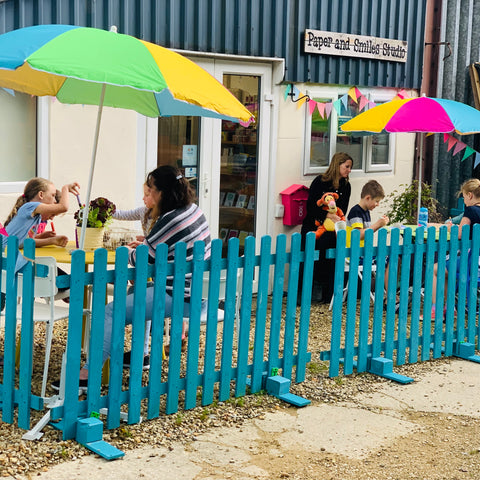 Image shows the outside of Paper and Smiles Studio.  There is a bright blue picket fence outside, picnic chairs and colourful parasols shade some families who are busy crafting in the sun.