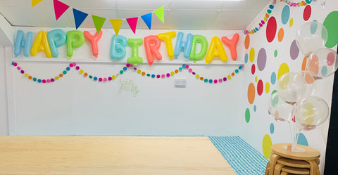 The image shows a the corner of a white room, filled with colourful bunting, balloons and a colourful inflated Happy Birthday Banner.  The walls have bright colourful circles on them.  There is a large plywood table surrounded by benches with turquoise cushions on them.