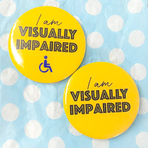 "A blue background with two yellow badges - each badge says ""I am Visually Impaired"" one also has a blue wheelchair icon"