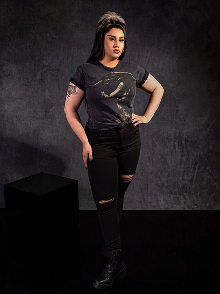 Jyoti Kaur standing in a staggered stance pose with the Alien™ Xenomorph in Repose Vintage Short Sleeve in Grey and ripped black jeans.