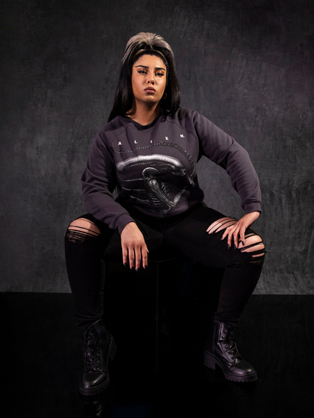 Jyoti Kaur sitting on a black box while wearing the Alien™ Xenomorph Profile Vintage-Style Cropped Sweatshirt from La Femme en Noir.