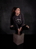 Micheline Pitt perched on a stone colored box while wearing the Alien™ Xenomorph Profile Vintage-Style Cropped Sweatshirt from La Femme en Noir.