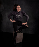 With her hands on her hips and one foot perched on a stone colored box, Micheline Pitt wears the Alien™ Xenomorph Profile Vintage-Style Cropped Sweatshirt.