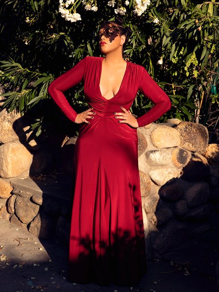 Ashleeta stands in a garden with her face shadowed by a tree while modeling the Art Deco gown in crimson.