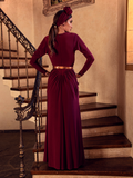 A back view of Aliza, standing on the staircase of a palatial home, models the Art Deco ruched gown in crimson from La Femme En Noir.