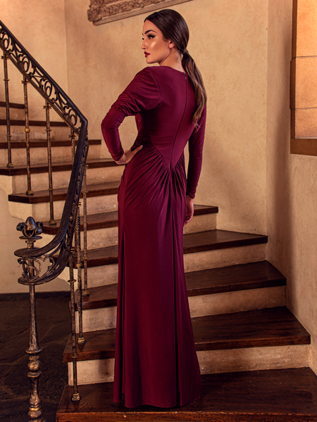 A back shot of Aliza, standing on a staircase with her hand on her hip, models the Art Deco ruched gown in crimson from La Femme En Noir.