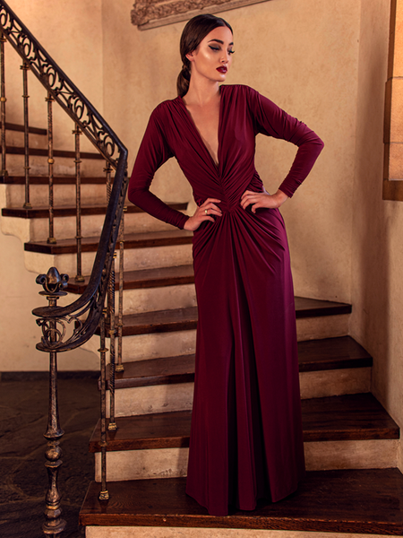 A full length shot of Aliza, standing on a staircase with her hands on her waist, models the Art Deco ruched gown in crimson from La Femme En Noir.