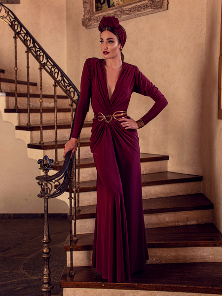 Aliza, standing on the staircase of a palatial home, models the Art Deco ruched gown in crimson from La Femme En Noir.
