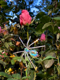 The Spider Baby Rhinestone Spider Brooch pictured against a pink rose garden.