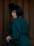 A back shot of Megan standing in front of a door with her hands in her pockets while modeling the Bauhaus top in hunter green.