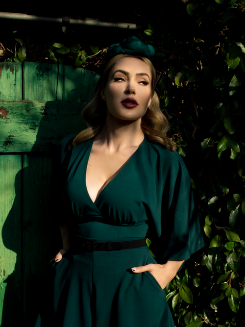 Micheline Pitt stands in a lush garden looking off camera while modeling the Bauhaus top in hunter green from La Femme En Noir.